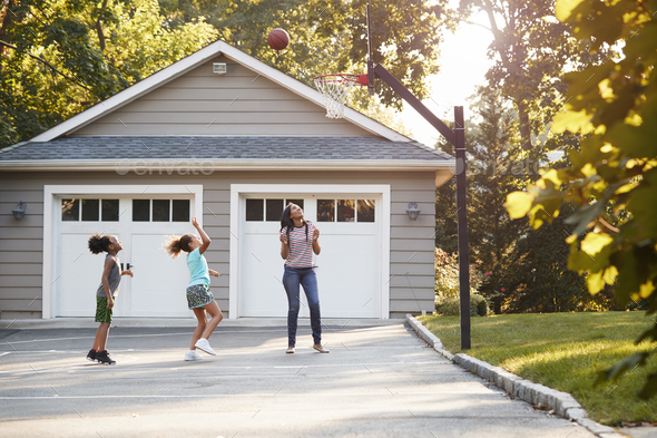 Mother And Children Playing Basketball On Driveway At Home - Stock Photo - Images