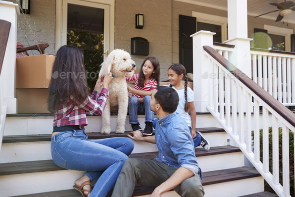 Family With Dog Sitting On Steps Of New Home On Moving In Day - Stock Photo - Images