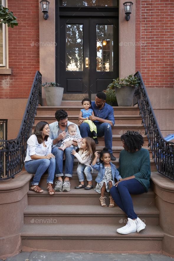 Two families with kids sitting on front stoops, vertical - Stock Photo - Images
