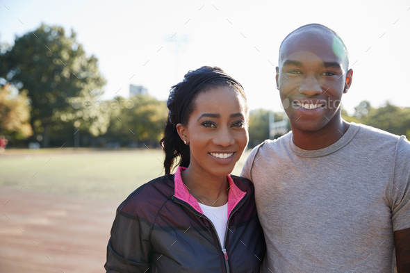 Young black couple smiling to camera in Brooklyn park - Stock Photo - Images