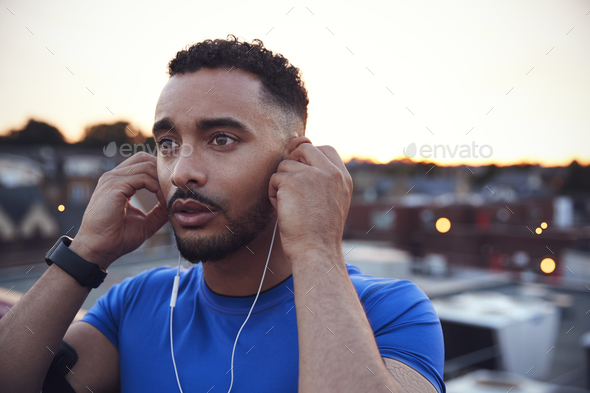 Male runner in urban setting adjusting earphones, close up - Stock Photo - Images