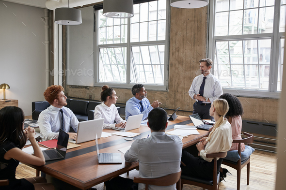 Bearded businessman addressing colleagues at a board meeting - Stock Photo - Images