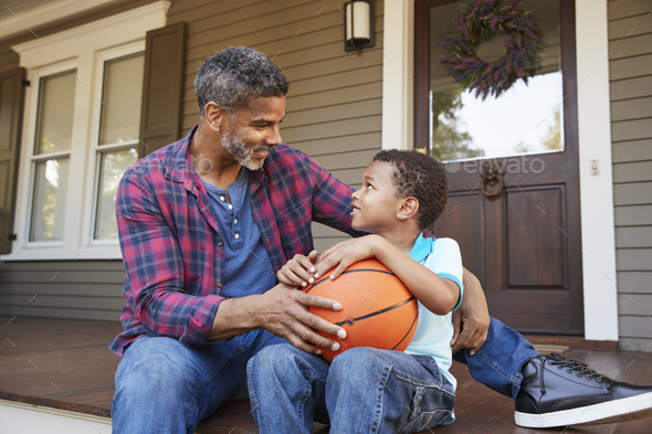 Father And Son Discussing Basketball On Porch Of Home - Stock Photo - Images