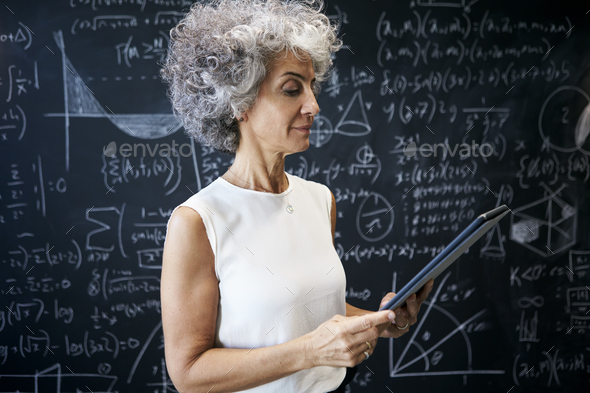 Middle aged academic woman working at blackboard - Stock Photo - Images