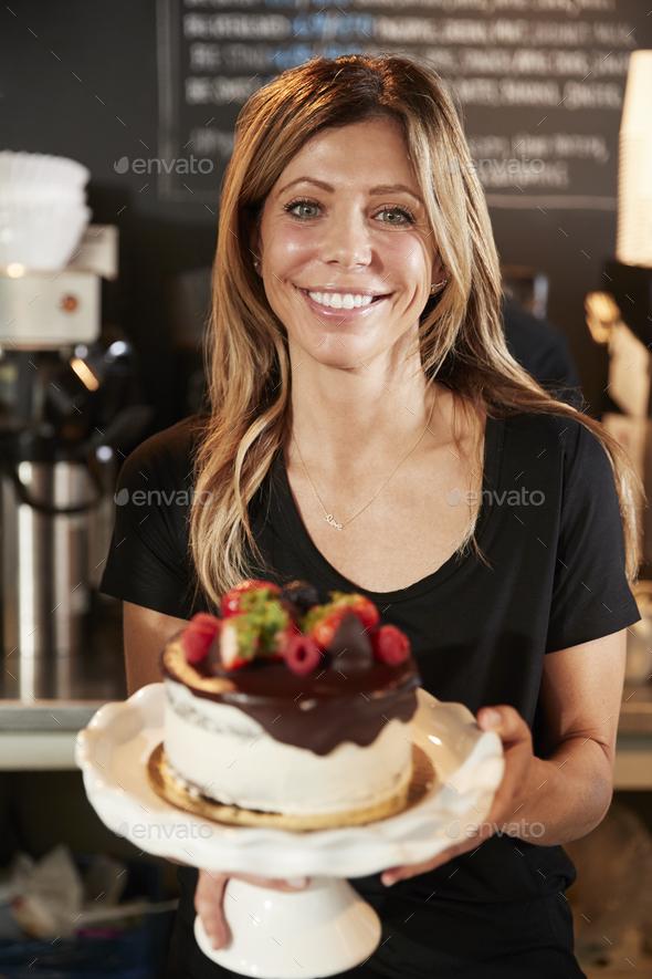 Waitress Holding Freshly Baked Cake With Buttercream Frosting - Stock Photo - Images