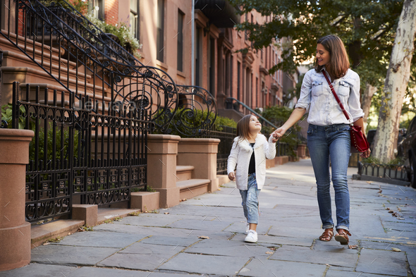 Mother and daughter walking down the street - Stock Photo - Images