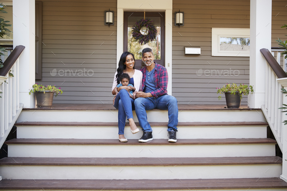 Family With Baby Son Sit On Steps Leading Up To Porch Of Home - Stock Photo - Images