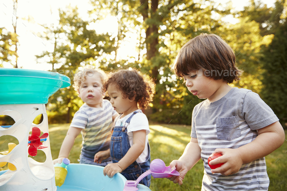 Group Of Young Children Playing With Water Table In Garden - Stock Photo - Images
