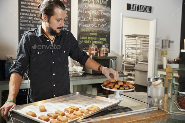Waiter Behind Counter In Coffee Shop Arranging Cookie Display - Stock Photo - Images