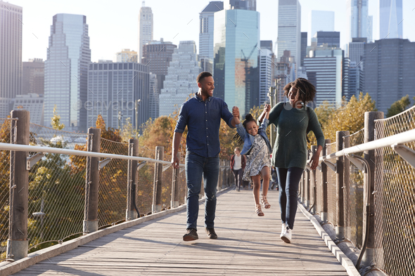 Young family with daughter taking a walk on footbridge - Stock Photo - Images