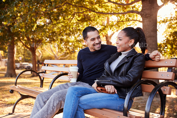 Young Hispanic couple sitting on bench in Brooklyn park - Stock Photo - Images