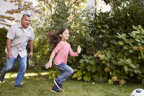 Grandfather Playing Soccer In Garden With Granddaughter - Stock Photo - Images