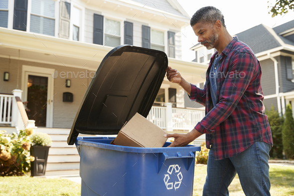 Man Filling Recycling Bin On Suburban Street - Stock Photo - Images