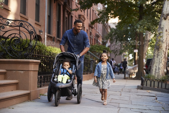 Father and two daughters taking a walk down the street - Stock Photo - Images