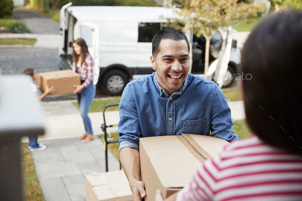 Children Helping Unload Boxes From Van On Family Moving In Day - Stock Photo - Images