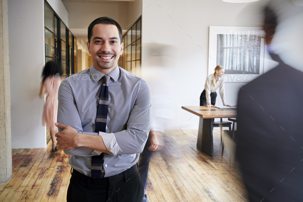 Portrait of young Hispanic man in a busy modern workplace - Stock Photo - Images