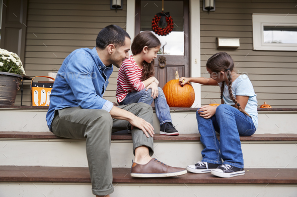 Father And Daughters Drawing Face On Halloween Pumpkin - Stock Photo - Images