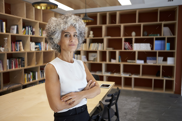 Senior businesswoman standing in boardroom looking to camera - Stock Photo - Images