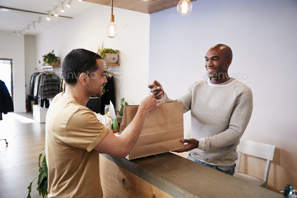 Man serving customer at the counter in a clothing store - Stock Photo - Images