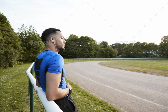 Male athlete wearing earphones taking a break at a track - Stock Photo - Images