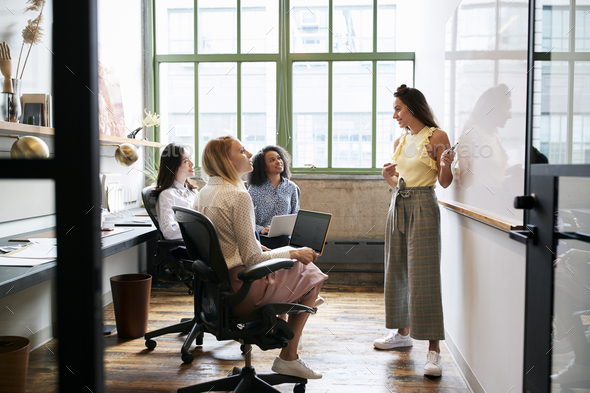 Woman standing at whiteboard in a meeting with female team - Stock Photo - Images