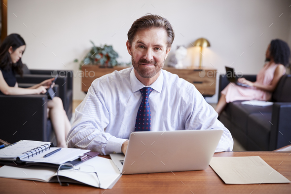 Businessman using laptop at desk smiling to camera - Stock Photo - Images