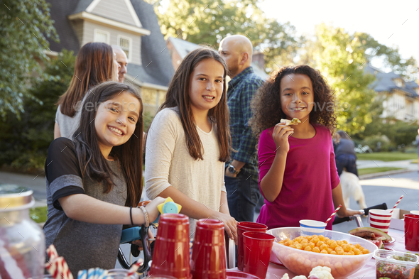 Pre-teen girls smiling to camera at a block party, close up - Stock Photo - Images