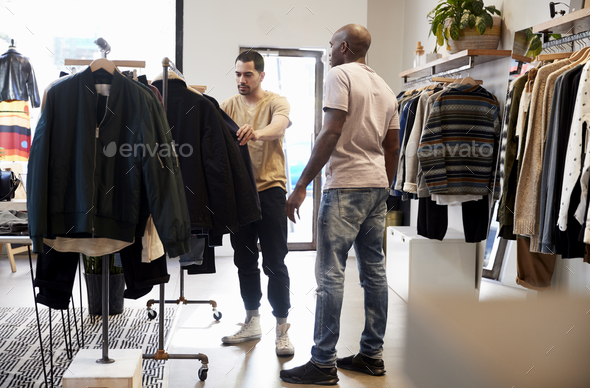 Shop assistant helping customer in a menÕs clothes shop - Stock Photo - Images