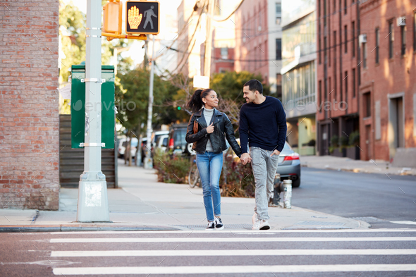Young Hispanic couple walk hand in hand in Brooklyn street - Stock Photo - Images
