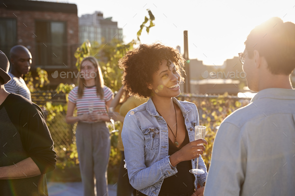 Friends talking at a rooftop party backlit by sunlight - Stock Photo - Images