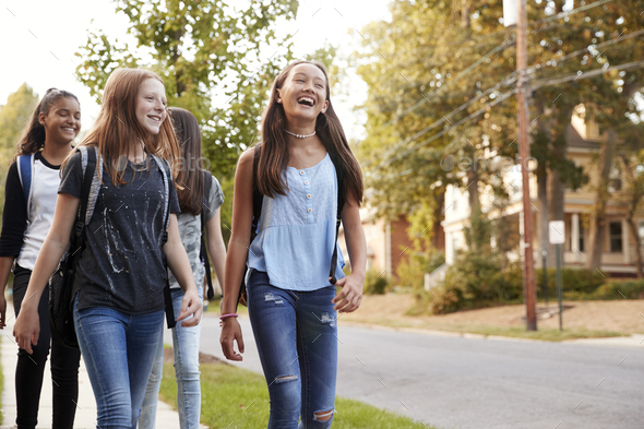 Four young teen girls walking to school, front view close up - Stock Photo - Images