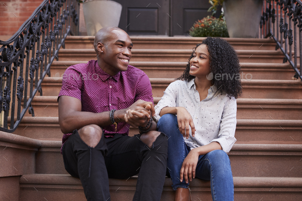 Couple Sit And Talk On Stoop Of Brownstone In New York City - Stock Photo - Images