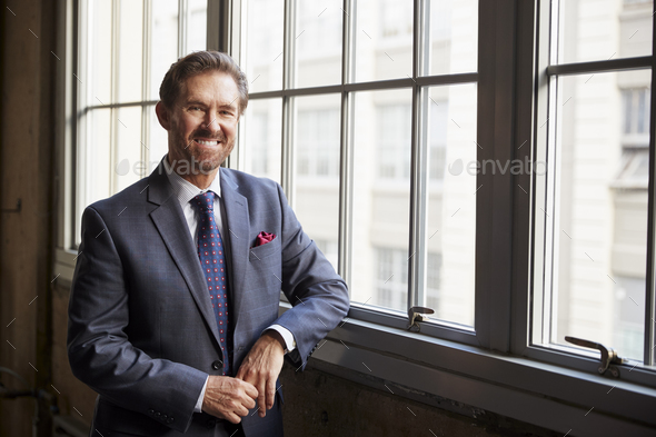 Senior white businessman smiling to camera - Stock Photo - Images