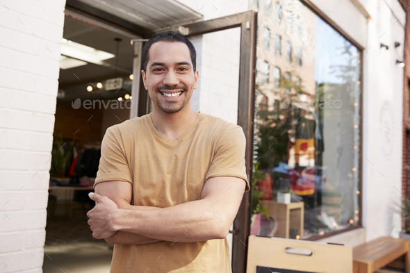 Young Hispanic shop owner smiling to camera outside his shop - Stock Photo - Images