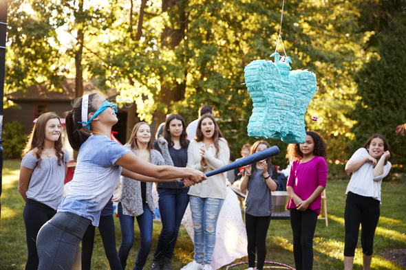 Friends watch teenage girl hitting a pi–ata on her birthday - Stock Photo - Images