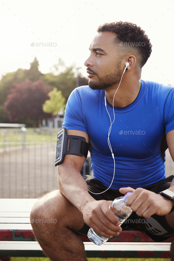 Young male athlete sitting on park bench holding water bottle - Stock Photo - Images