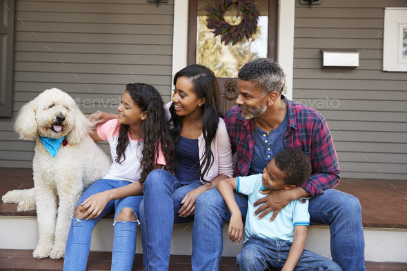 Family With Children And Pet Dog Sit On Steps Of Home - Stock Photo - Images