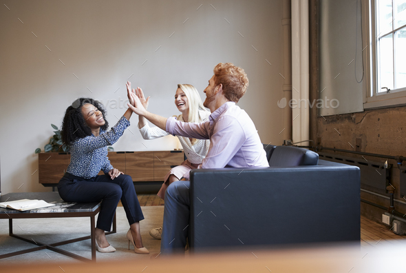 Three colleagues high five at a casual work meeting - Stock Photo - Images