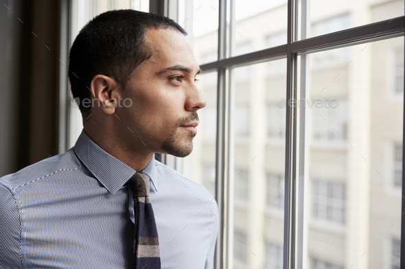Young Hispanic business man looking out of window - Stock Photo - Images