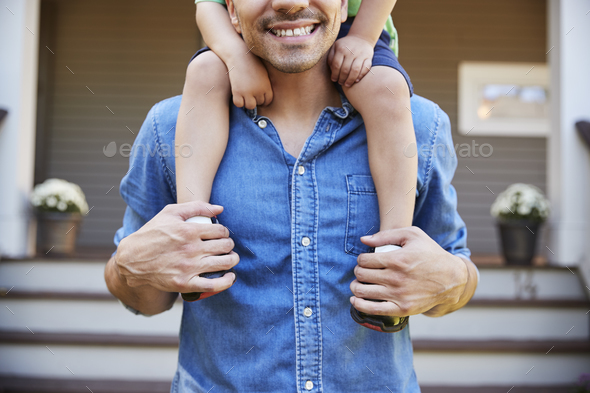 Father Giving Son Ride On Shoulders Outside House - Stock Photo - Images