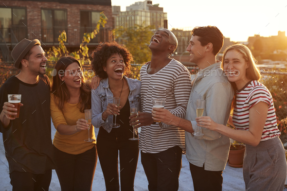 Friends drinking and laughing at a rooftop party in Brooklyn - Stock Photo - Images