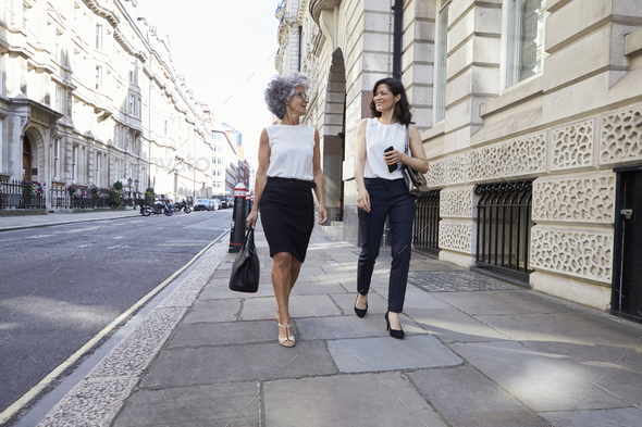 Two female colleagues walking in the street talking - Stock Photo - Images