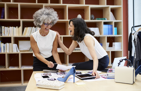 Two happy women talking in a creative media office, close up - Stock Photo - Images