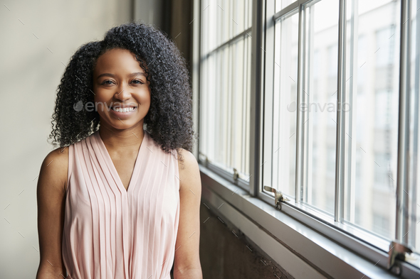 Young black business woman by window looking to camera - Stock Photo - Images