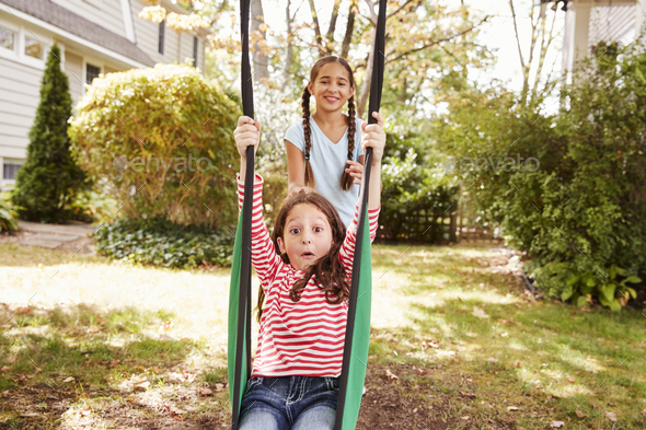 Two Sisters Having Fun On Garden Swing At Home - Stock Photo - Images
