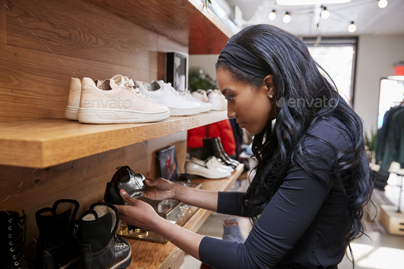 Young woman looking at shoes on display in a shop, close up - Stock Photo - Images