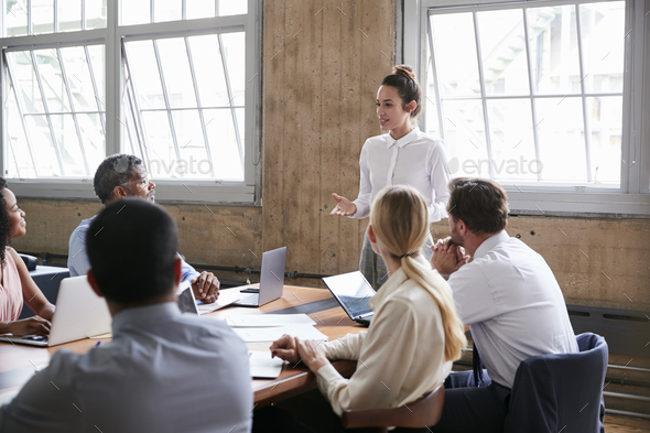 Female manager addressing team at board meeting gesturing - Stock Photo - Images