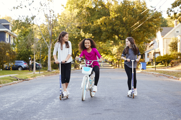 Three pre-teen girls riding in street on scooters and a bike - Stock Photo - Images