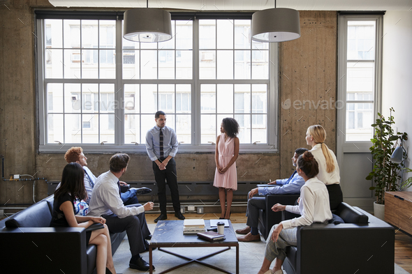Man and woman present to team at informal business meeting - Stock Photo - Images
