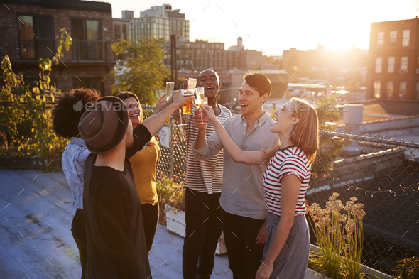 Friends make a toast at a rooftop party, backlit by sunlight - Stock Photo - Images
